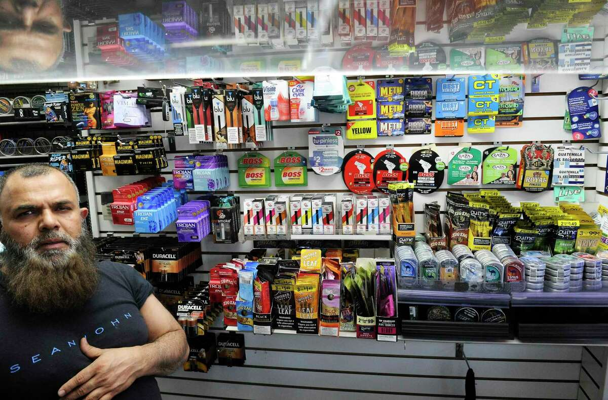 A clerk of Stamford Photo and News on Jan, 8, 2020 in Stamford, Conn., stands behind the counter of the convenience store with an assortment of e-vaping and tobacco products that the retailer offers for sale.