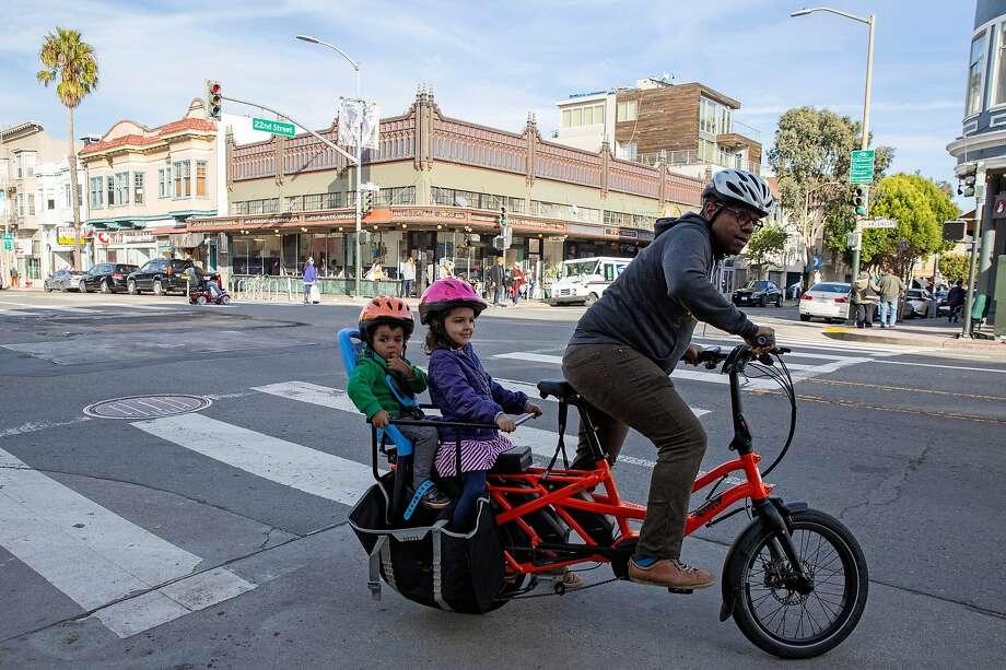 Ed Parillon rides a cargo e-bike in San Francisco, carrying his son, Simon, 2, and daughter, Louise, 4. Photo: Santiago Mejia / The Chronicle