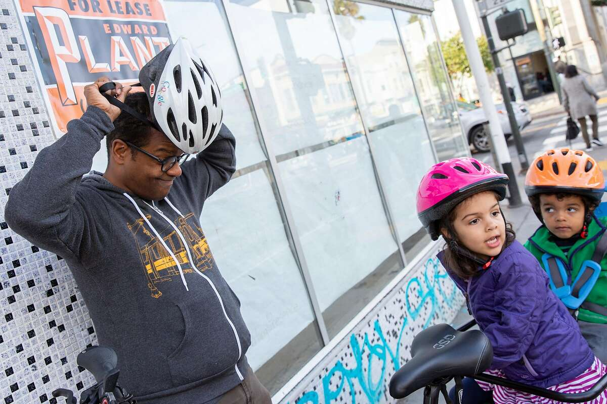 From left: Ed Parillon with his children Louise Parillon, 4, and Simon Parillon, 2, on a bike on Friday, Jan. 3, 2020, in San Francisco, Calif. Parillon runs errands and uses a bike instead of a car.