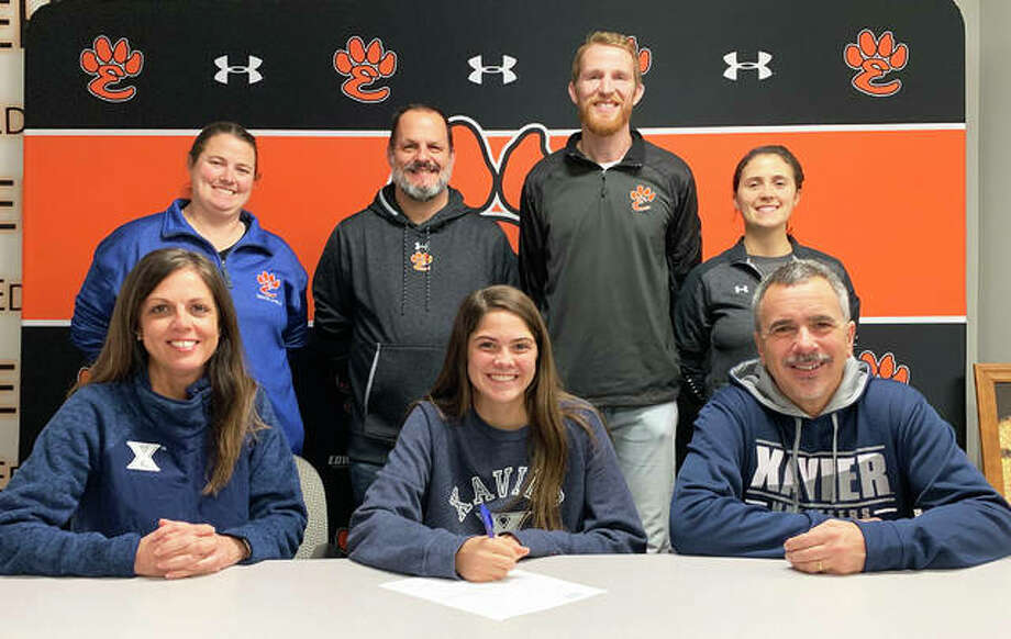 Edwardsville senior Abby Korak, seated center, will compete in track and field and cross country for Xavier University in Cincinnati. She is seated with her parents and joined by EHS track and field coach Camilla Eberlin, standing left, EHS cross country coach George Patrylak, standing second to left, EHS assistant coach Dustin Davis, standing second to right, and EHS assistant coach Maggie Dust. Photo: Matt Kamp|The Intelligencer