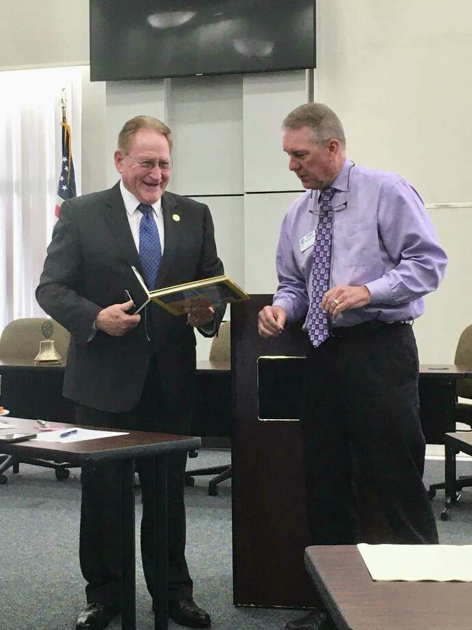 """County Judge Mark Keough accepted a book to sign for Runyan Elementary from Rotary Club of Conroe President Denny Buckalew at last Tuesday's meeting. Keough gave a """"State of the County"""" program at the RCC club meeting. Photo: Photo By Sondra Hernandez"""