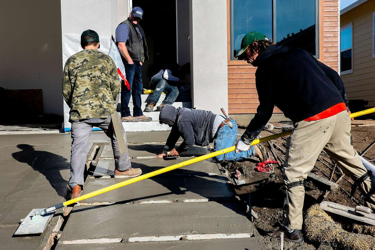 Evans Construction Inc. workers craft the concrete for a driveway and front steps for a new home along Hopper Avenue the Coffey Park neighborhood on Friday, Jan. 10, 2020, in Santa Rosa, Calif.