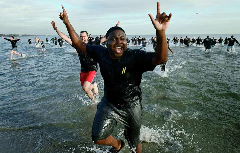 Junior analyst Rubin St. Martin and over 100 other employees of Synchrony, a premier consumer financial services company, participate in the fifth annual Doubles Dive Friday, January 10, 2020, plunging into the chilly waters to raise money for charity at Compo Beach in Westport, Conn. The benefit event was conceived in 2015 by Synchrony president Brian Doubles and has grown to 14 other Synchrony sites throughout the U.S., India and the Philippines. Funds raised from this years Doubles Dive will go to SeriousFun Children's Network, a global community of 30 camps and programs providing life-changing experiences to children living with serious illnesses and their families free of charge. Photo: Erik Trautmann / Hearst Connecticut Media / Norwalk Hour