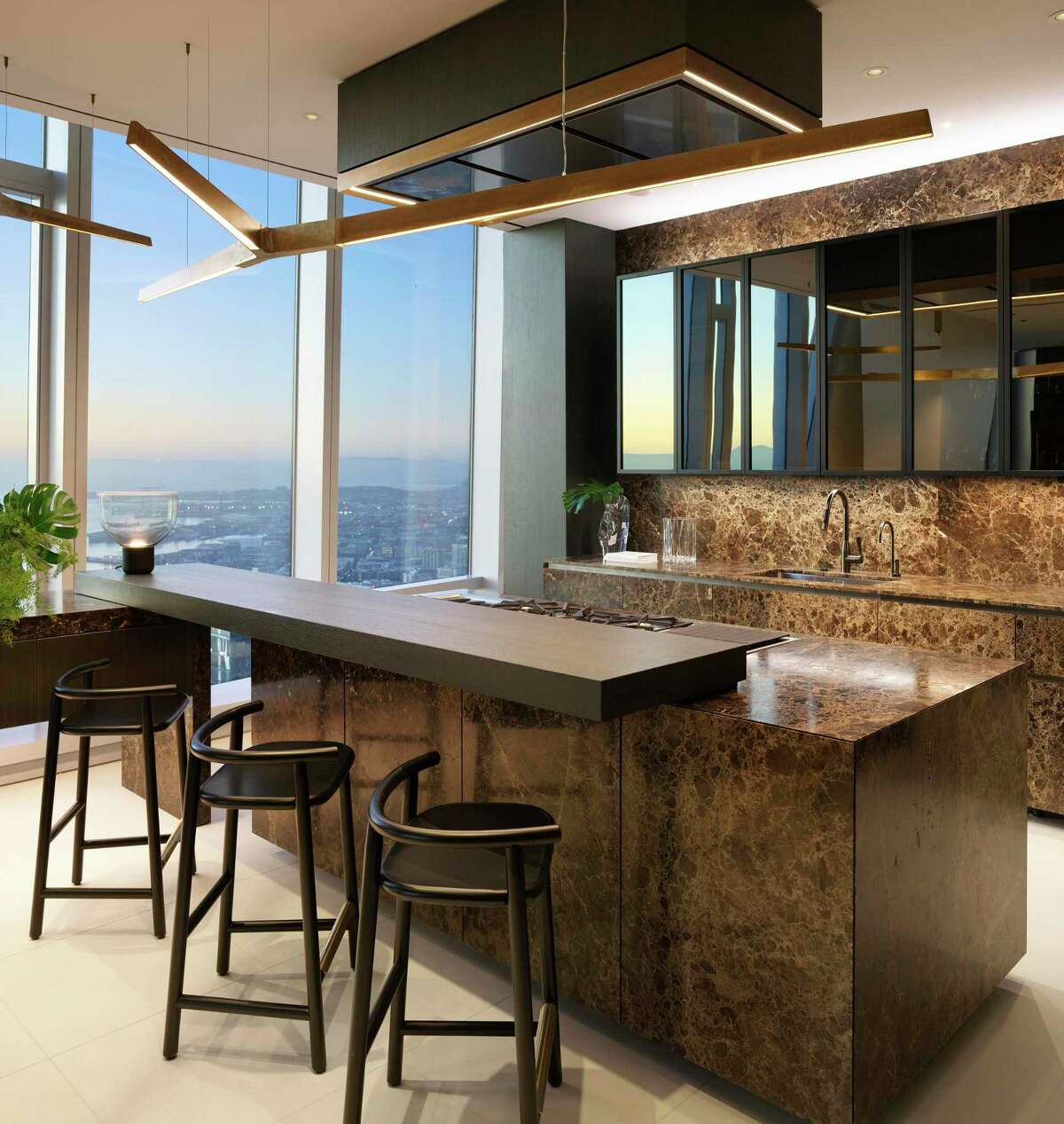 Limestone flooring, with Rossana custom kitchen cabinets and counter seating, Gaggenau appliances including refrigerator and freezer tower, double ovens, wine tower, dishwasher, five-burner cooktop, grill, and teppanyaki station finish the exhibition kitchen at the Grand Penthouse of 181 Fremont.