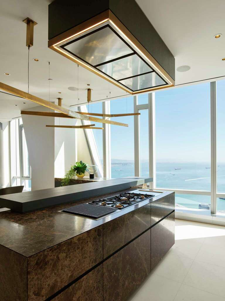 <p>The exhibition kitchen within the grand penthouse at 181 Fremont overlooks the family room, while floor-to-ceiling windows frame views of the bay.</p>