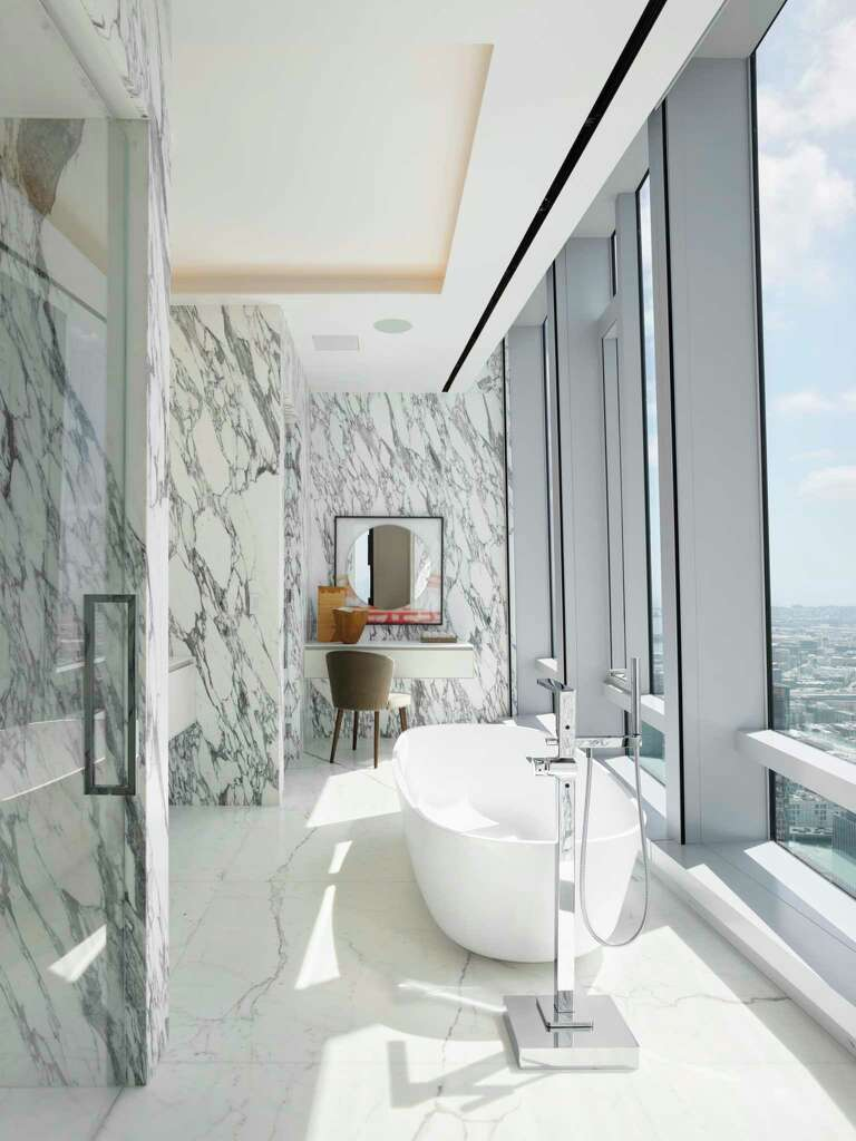 <p>The master suite of the grand penthouse at 181 Fremont features a pair of spa bathrooms, this one boasting an oval soaking tub and steam shower looking out over the City to the Pacific Ocean.</p>