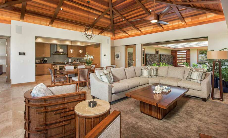 Tile flooring lines a voluminous living room sheltered by a wood-paneled ceiling. Photo: The Residences At Laule'a