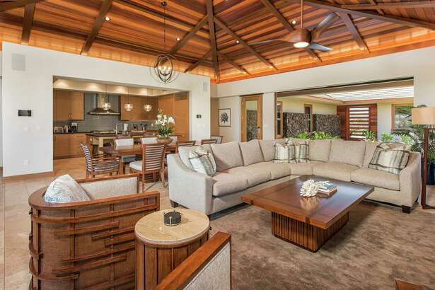 Tile flooring lines a voluminous living room sheltered by a wood-paneled ceiling.