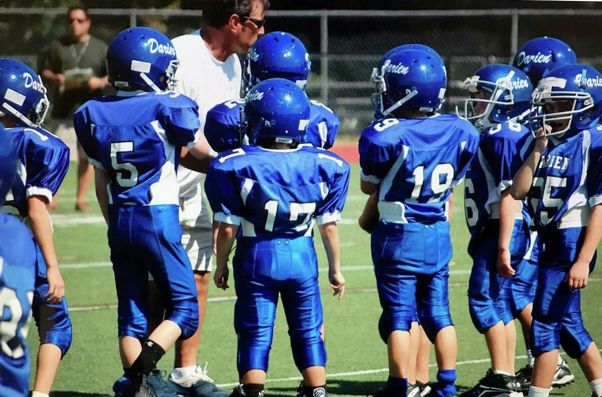 Darien High School football coach Rob Trifone works with the Darien Junior Football League's third-grade team during the 2010 season. Trifone has coached that group of players for the past 10 seasons, and many are seniors on his 2019 Blue Wave varsity team.