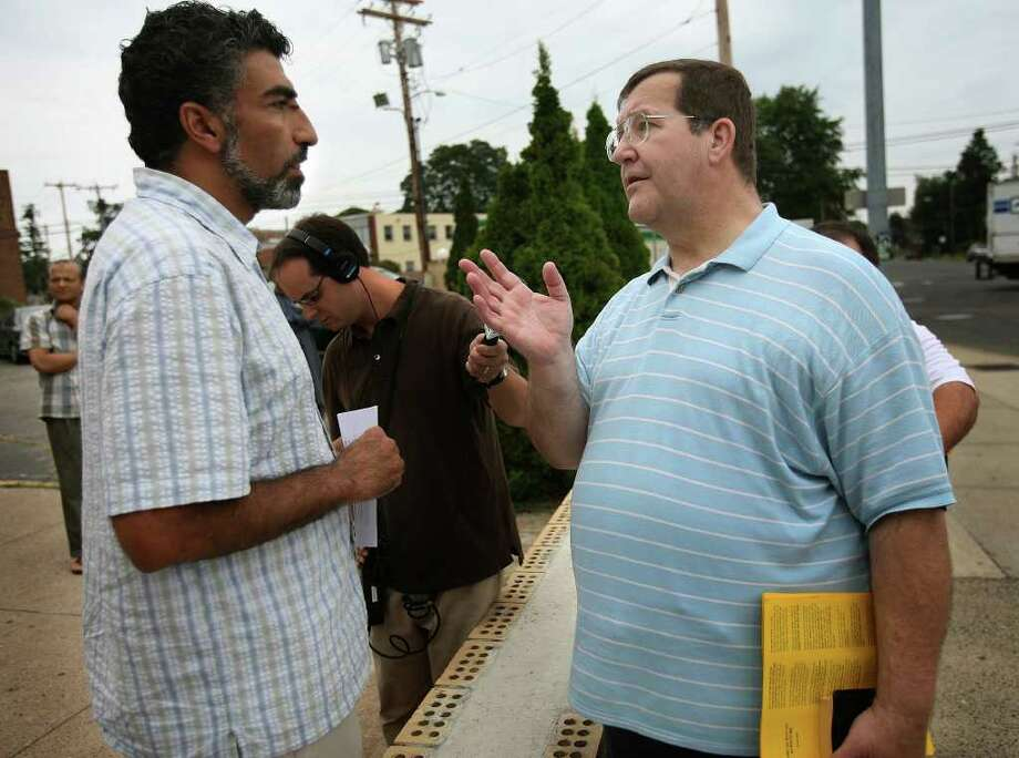 Mongi Dhaouadi, left, executive director of the Council on American Islamic Relations, talks with Christian protestor John Payne of Milford outside Masjid An-Noor mosque on Fairfield Avenue in Bridgeport on Thursday, August 12, 2010. Tensions have been high since Chrsitian protestors began handing out anti-Islamic literature outside the mosque. Photo: Brian A. Pounds / Connecticut Post