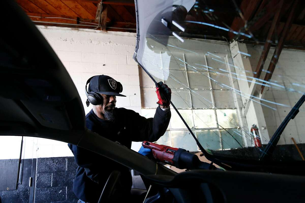 Zane Maxie, Auto Glass technician, removes a cracked windshield from a car while replacing it at Auto Glass Now on Friday, January 10, 2020 in Oakland, Calif.