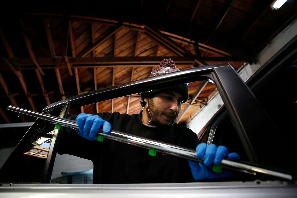 Devontae Briscoe, auto glass technician, puts back pieces onto a car as he replaces a rear passenger window on car at Auto Glass Now on Friday, January 10, 2020 in Oakland, Calif.