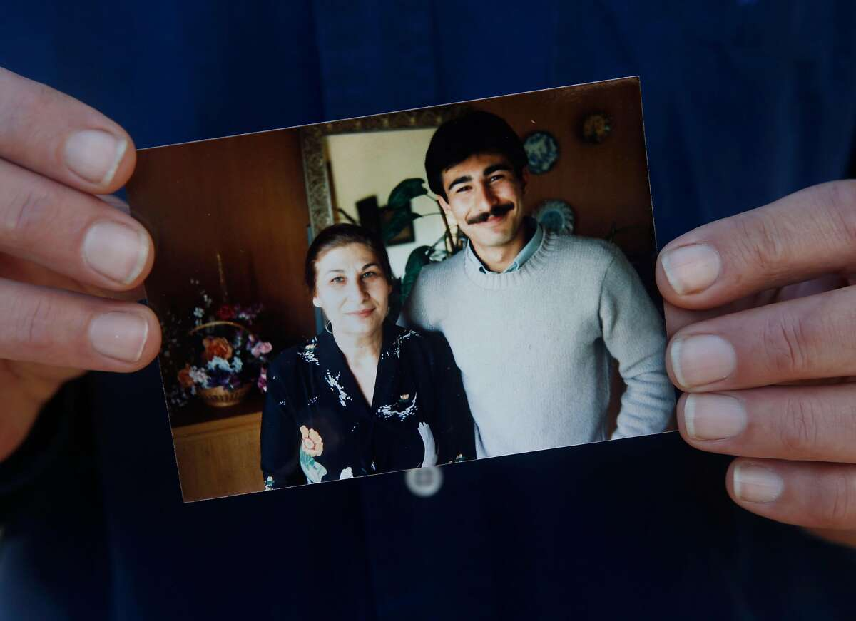 Sadri Madjlessi holds a photograph from 1985 of himself posing with his mother Pouri, in Oakland, Calif. on Friday, Jan. 10, 2020. Madjlessi is reluctant to return to his native country of Iran to mourn the passing of his mother due to the escalating tensions between the U.S. and Iran.
