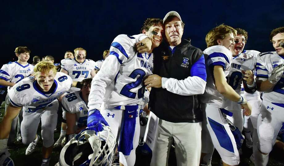 Darien head coach Rob Trifone embraces his son, Robby Trifone, celebrating their victory over the Shelton Gaels, 39-7, for the Class LL state football championship in 2015.. Photo: Hearst Connecticut Media File Photo / Catherine Avalone/New Haven Register