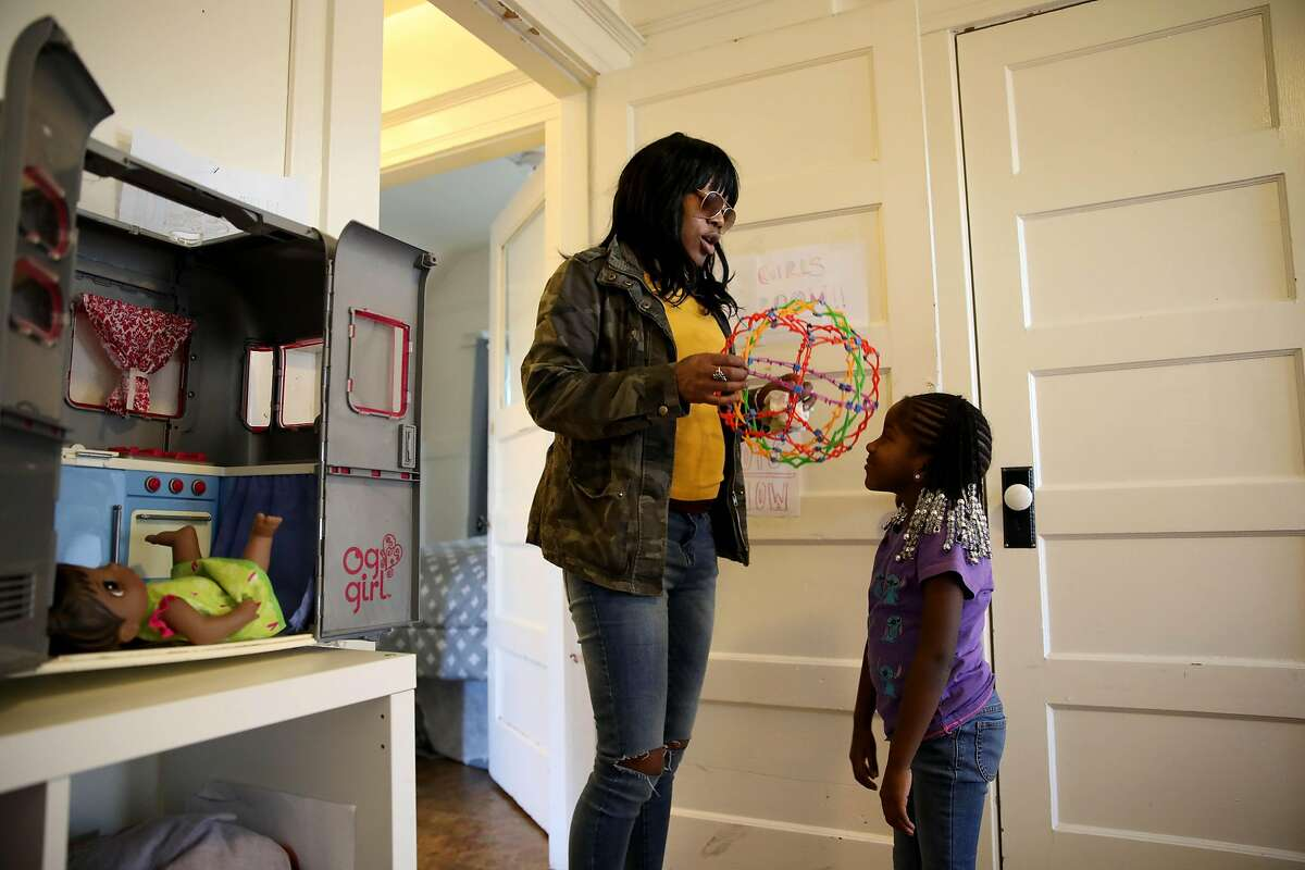 Misty Cross, 39, converses with her daughter, Demi Johnson, 5, inside the Magnolia Street home in Oakland, Calif., on Friday, January 10, 2020.