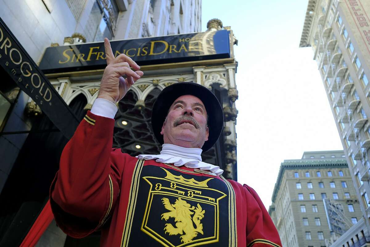 Beefeater doorman Tom Sweeney points up Powell Street while standing outside the Sir Francis Drake Hotel in San Francisco. The hotel is reportedly considering a name change.