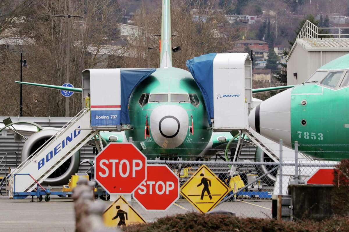 FILE - In this Monday, Dec. 16, 2019, file photo, Boeing 737 Max jets sit parked in Renton, Wash. Newly released Boeing documents show that company employees knew about problems with flight simulators for the now-grounded 737 Max jetliner and talked about misleading regulators. (AP Photo/Elaine Thompson, File)