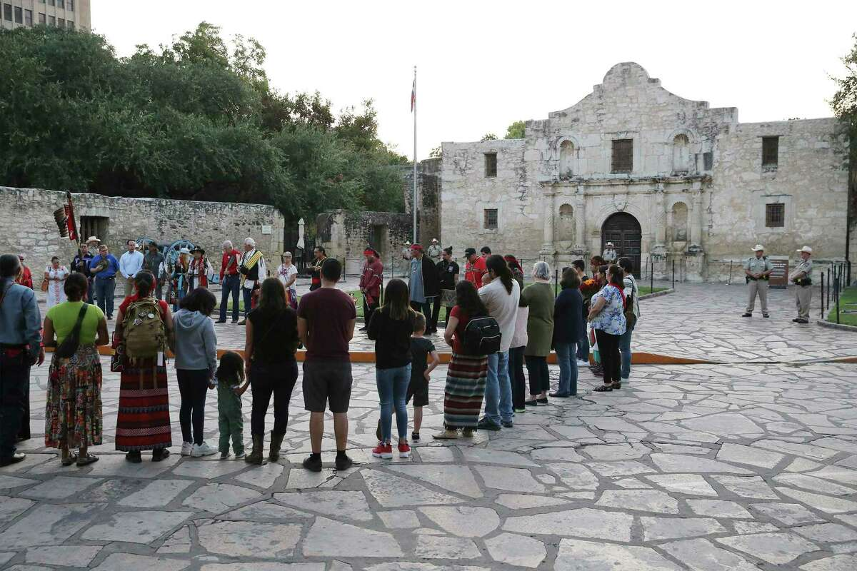 A local Native American group honored buried descendants during their 25th Annual Sunrise Ceremony at the Alamo on Saturday, Sept. 7, 2019. Ramon Juan Vasquez, executive director of American Indians in Texas at the Spanish Colonial Missions, along with over 60 people who claim ancestry with the Native Indians who are buried on the grounds of the Alamo, formed a circle in front of the church to pray and honor their descendants. In the past, the group was allowed to have the service inside the chapel but were told days before the event that the service would not be permitted inside the Alamo. With a noticeable presence of Alamo security officers and chain blocking the walking to the front doors, the group formed a circle on Alamo Plaza to air their grievances and to remember their descendants. Vasquez and the group was joined by State Senator Jose Mendendez, State Rep. Leo Pacheco and Poet Laureate Carmen Tafolla who all expressed dismay that the indigenous group would not be allowed to pray and honor their loved ones inside the Alamo. Despite the prohibition, members of the Tap Pilam Coahuiltecan Nation and other indigenous people paid their respects on the ground by the front of the Alamo. A shell filled with sage slowly burned and filled the early morning sky with wafts of smoke - which traditionally serves to bless and purify - as the service ended just as the sun rose over the Alamo. (Kin Man Hui/San Antonio Express-News)