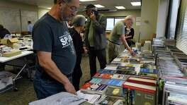 """Jose Castillo, a long-time listener of public radio, looks through books during a """"garage sale"""" at Texas Public Radio headquarters on Friday, Jan. 10, 2020. Texas Public Radio is preparing its move from its high-rise offices near the Medical Center to the Alameda Theater complex in downtown San Antonio next month."""