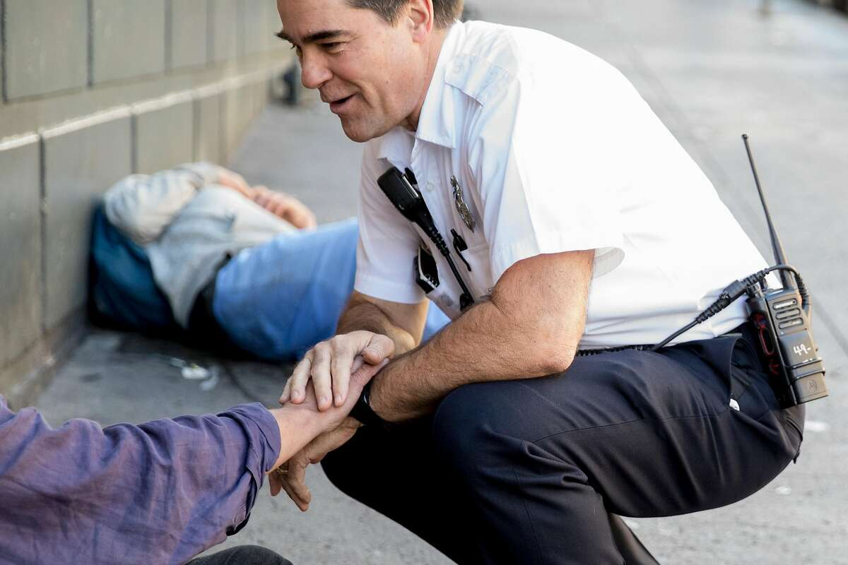EMS-6 Captain Scott Eberhart greets a familiar face while walking the Tenderloin to identify at-risk homeless people during a high-intensity care team shift managing and facilitating high-impact patient cases of those suffering from addiction and mental illness on the streets in San Francisco, Calif. Friday, Jan. 10, 2020.