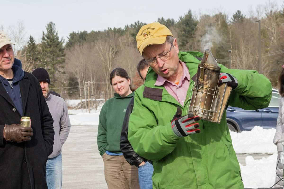 Connecticut Beekeepers Association President Steve Dinsmore demonstrates the lighting and use of a smoker to beekeeping school participants.
