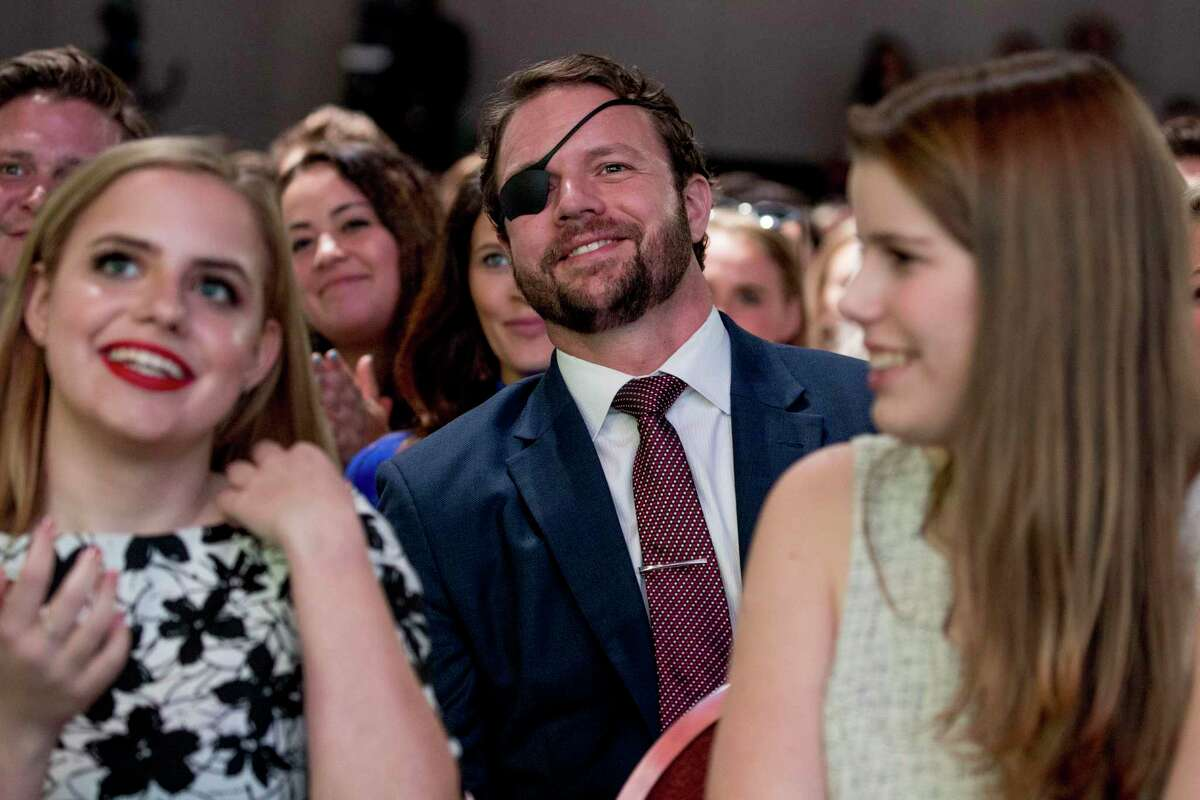 Rep. Dan Crenshaw, R-Texas, center, smiles as President Donald Trump calls out to him as he speaks at the Turning Point USA Student Action Summit at the Palm Beach County Convention Center in West Palm Beach, Fla., Saturday, Dec. 21, 2019.