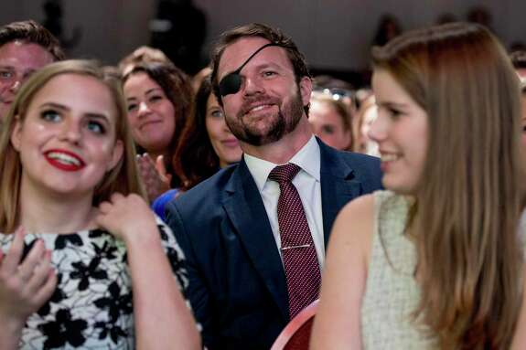 Rep. Dan Crenshaw, R-Texas, center, smiles as President Donald Trump calls out to him as he speaks at the Turning Point USA Student Action Summit at the Palm Beach County Convention Center in West Palm Beach, Fla., Saturday, Dec. 21, 2019. (AP Photo/Andrew Harnik)