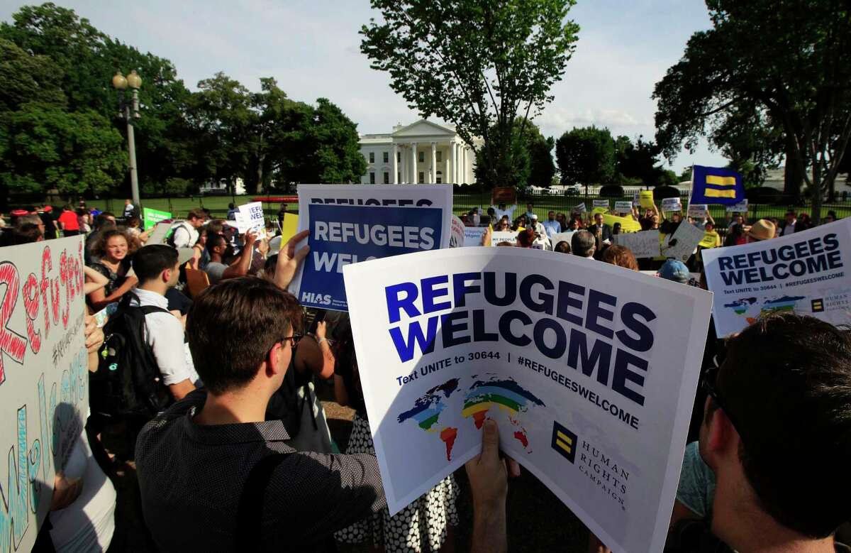 FILE - In this June 20, 2017 file photo, refugees and community activists gather in front of the White House in Washington. The Trump administration wants to cap the number of refugees admitted into the United States to the lowest number since the resettlement program was created in 1980.