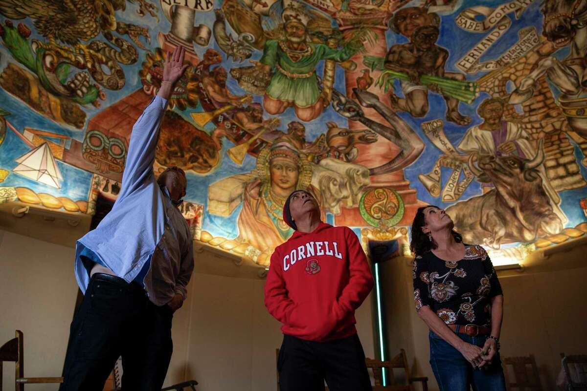"""Docent Mark Mondragón, left, explains parts of the a Buon fresco titled """"Mundos de Mestizaje"""" by Frederico Vigil to Mario Aguilar and Maria Appelzoller at the National Hispanic Cultural Center in Albuquerque, NM. The buon fresco located in the Torreon took ten years to complete and depicts thousands of years of Hispanic and pre-Hispanic history."""