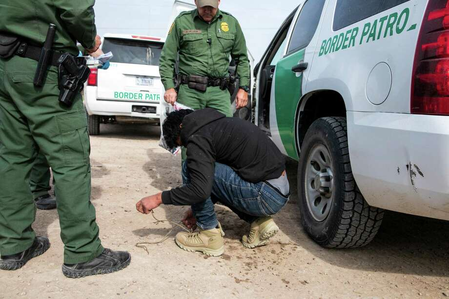 Customs and Border Protection officers apprehend a teenager from Guatemala, who officials said was slowed down by the border wall, in Peñitas, Texas, Dec. 12, 2019. Construction of President Donald Trump's border wall has been slow going, in part because the Texans who own the land have to be coaxed or coerced to sell it, whether they want to or not. (Ilana Panich-Linsman/The New York Times) Photo: ILANA PANICH-LINSMAN, STR / NYT / NYTNS