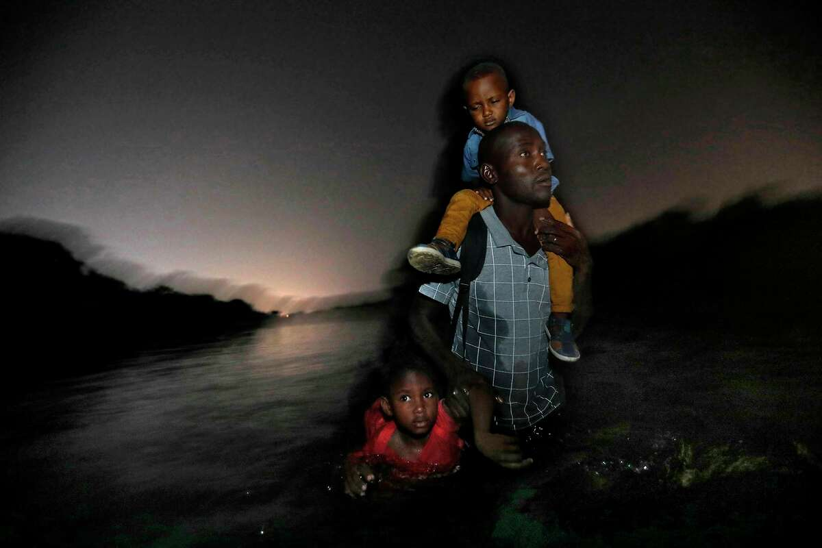 """A Haitian man carries one child on his shoulders and drags another by his arm as he wades across the Rio Grande River to Del Rio, Texas on in June 2018. Texas Gov. Greg Abbott said Friday that the state will stop the re-settlement of new refugees, becoming the first state known to do so under a recent Trump administration order. He said it had to deal with """"disproportionate migration issues resulting from a broken federal immigration system."""""""