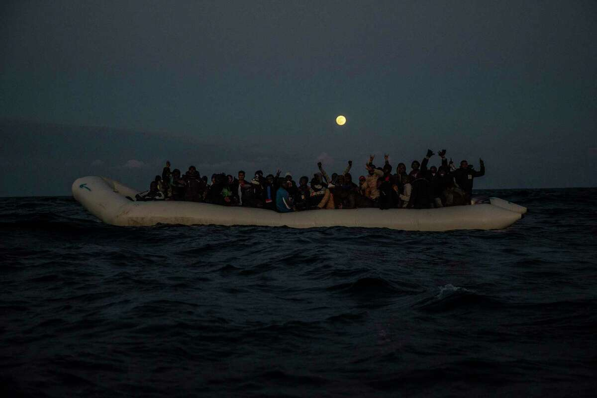 Migrants and refugees from different African nationalities react on an overcrowded wooden boat, as aid workers of the Spanish NGO Open Arms approach them in the Mediterranean Sea, international waters, off the Libyan coast, in January 2020. Texas Gov. Greg Abbott said Friday that the state will stop the re-settlement of new refugees, becoming the first state known to do so under a recent Trump administration order.