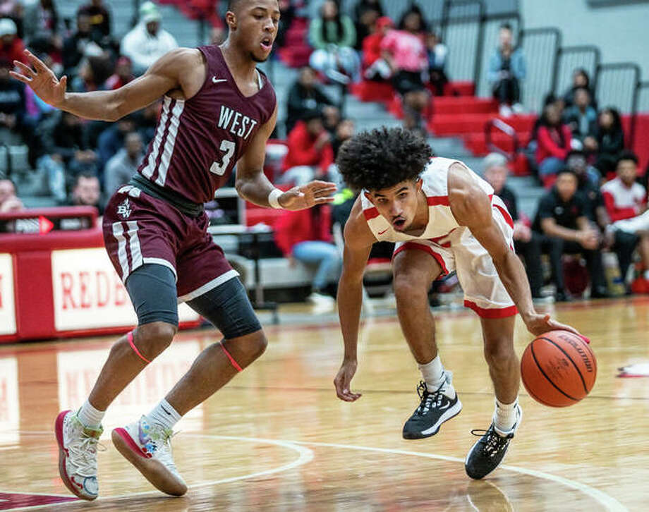 Alton senior guard Andrew Jones secures a loose ball as Belleville West's Tommie Williams defends Friday night in Southwestern Conference action at Alton High. Photo: Nathan Woodside | The Telegraph