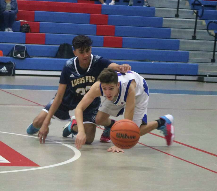 FBCA point guard Nick Gay attempts to win a loose ball battle with a Logos Prep player during second-half action Friday night. Gay kept the ball but the Sugar Land school kept the victory. Photo: Robert Avery