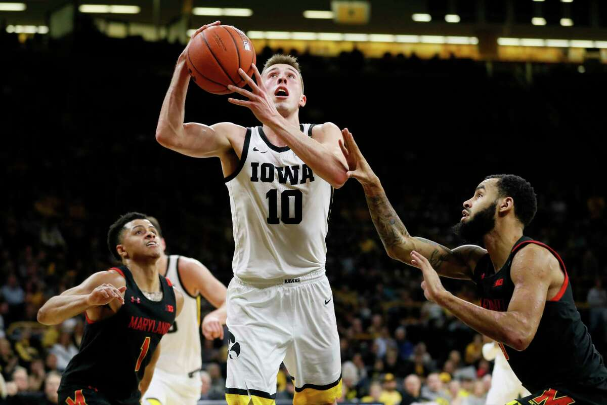 Iowa guard Joe Wieskamp (10) drives to the basket between Maryland's Anthony Cowan Jr., left, and Eric Ayala, right, during the second half of an NCAA college basketball game, Friday, Jan. 10, 2020, in Iowa City, Iowa. (AP Photo/Charlie Neibergall)