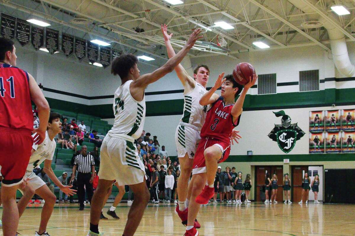 Clear Lake's Alex Lee (3) tries to put up a shot over Clear Falls' Carson Lindsey (24) and Von Wells (0) Friday at Clear Falls High School.