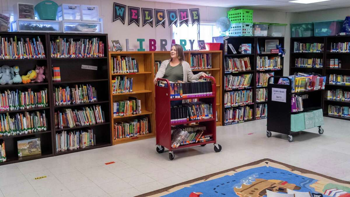 Tanya Burges works putting books out in the library room. The school has been rebuilding their collection to replace those destroyed by the storm. Oak Forest Elementary School has been operating in a number of portable classrooms since the school was decimated by Hurricane Harvey three years ago. Photo made on Wednesday, January 8, 2020. Fran Ruchalski/The Enterprise