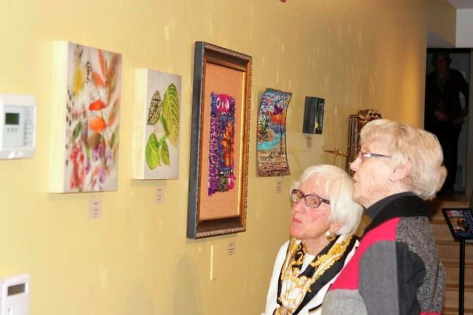 Visitors check out a wall of varied artwork at the Furniture, Fiber, Photography and Sculpture exhibit at the Oliver Art Center. (Photo/Colin Merry)