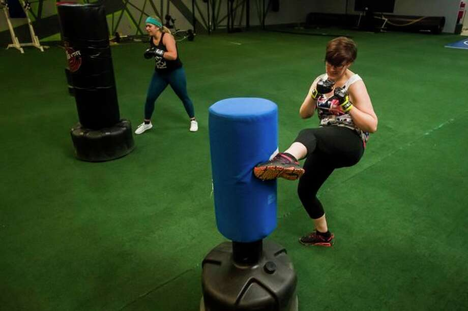 Amanda Austin of Essexville, left, and Adrienne Gibson of Hope, right, kick punching bags during a kickboxing class Thursday at Edge Fitness and Training Headquarters in Midland. (Katy Kildee/kkildee@mdn.net)