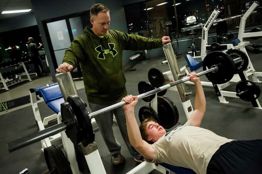 FILE — Dean Wolfe lifts weights as his father, Eric Wolfe, spots him in January at Edge Fitness and Training Headquarters in Midland. (Katy Kildee/kkildee@mdn.net)