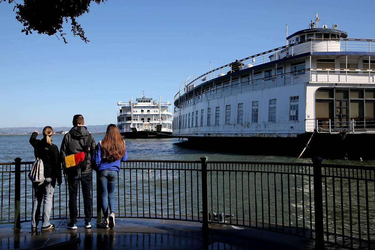 (Left to right) Lindsay Gore, John Hanna, and Vivian Hanna, stand between piers 3 and 5 at the bay side, as they observe the water following a King Tides presentation sponsored by the Exploratorium, a science museum, in San Francisco, Calif., on Saturday, January 11, 2020. A king tide is expected on Saturday with a high tide of nearly 7 feet at Pier 41 at 11:20 a.m.