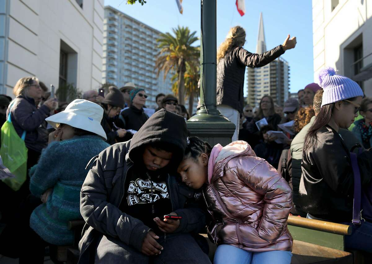 Siblings Kalil Jaylon Jones, 10, and Kaliyah Jones, 7, who are also students from Markham Elementary School in Oakland, look at a phone as Lori Lambertson, staff educator, Exploratorium, speaks during a King Tides presentation sponsored by the Exploratorium, a science museum, between piers 3 and 5 at the bay side, in San Francisco, Calif., on Saturday, January 11, 2020. A king tide is expected on Saturday with a high tide of nearly 7 feet at Pier 41 at 11:20 a.m.