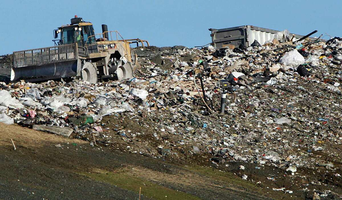 In this Dec. 6, 2012 file photo, trash is compacted at the landfill in Moretown, Vt. Americans are sending more than twice as much trash to landfills than the federal government estimates, according to a new study.