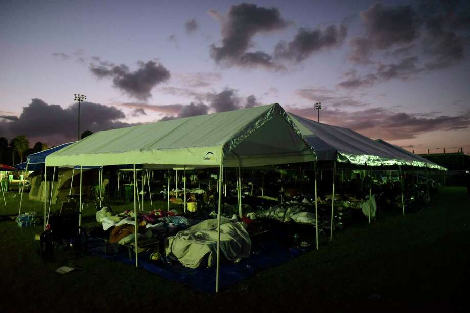 Tents and cots are set up for people whose homes are either destroyed or unsafe to enter after an 6.4 magnitude earthquake, at a baseball stadium amid aftershocks and no electricity in Guayanilla, Puerto Rico, at sunrise Friday, Jan. 10, 2020. Hundreds of thousands of Puerto Ricans are still without power and water, and thousands are staying in shelters and sleeping on sidewalks since Tuesday's earthquake. (AP Photo/Carlos Giusti) Photo: Carlos Giusti / Associated Press / Copyright 2020 The Associated Press. All rights reserved.