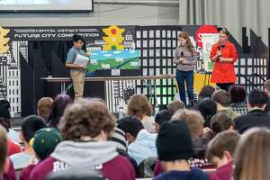 Students from Hackett Middle School in Albany, Saugat Shah, Zoey Volmer and Barbara Kirchgraber, present the city of Viridian to a panel of judges during the annual National Engineers Week Future City Competition held at the Sage College Armory on Saturday, Jan. 11, 2019 (Jim Franco/Special to the Times Union.)