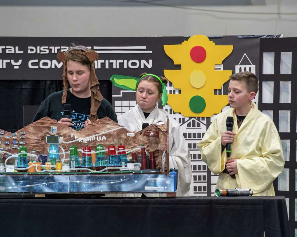 Broadalbin Middle School students Trenton Richmond, Emma Watermann and Owen Compani, dressed as the Star Wars characters, present the city of Terraqua to a panel of judges during the annual National Engineers Week Future City Competition held at the Sage College Armory on Saturday, Jan. 11, 2019 (Jim Franco/Special to the Times Union.)