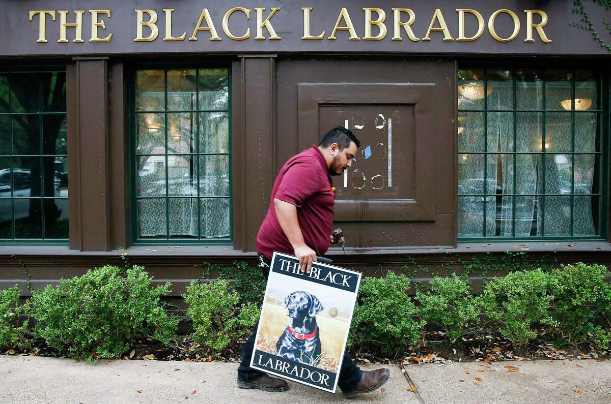 Richard Rodriguez walks with a freshly-removed sign for The Black Labrador, a long-time English pub mainstay in the Montrose neighborhood on Friday, Jan. 10, 2020 in Houston. Rodriguez took the sign for the building's owner.