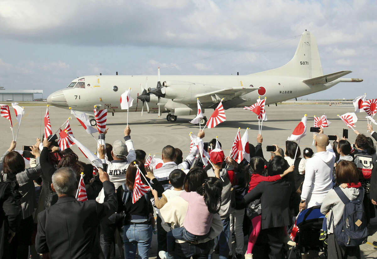 A Maritime Self-Defense Force P-3C patrol plane departs from the Naha Air Base in Okinawa Prefecture on Saturday morning as the families of SDF personnel wave them off.