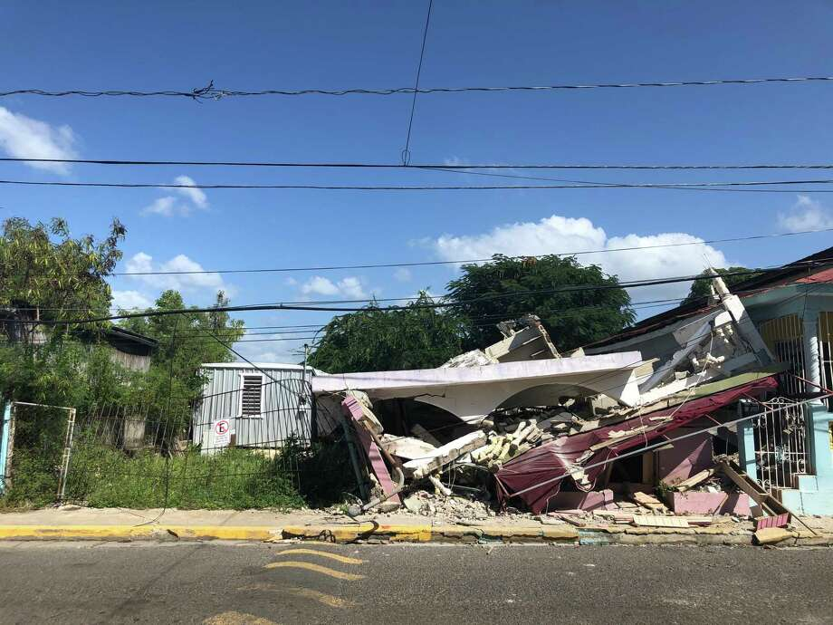 A house collapsed across the street from Angelica Hernández's home in Guánica, Puerto Rico. She fled with her family last week after powerful earthquakes cracked the ceiling. They are now living at a government-run camp for people displaced by the disaster. Photo: Washington Post Photo By Arelis R. Hernandez / The Washington Post