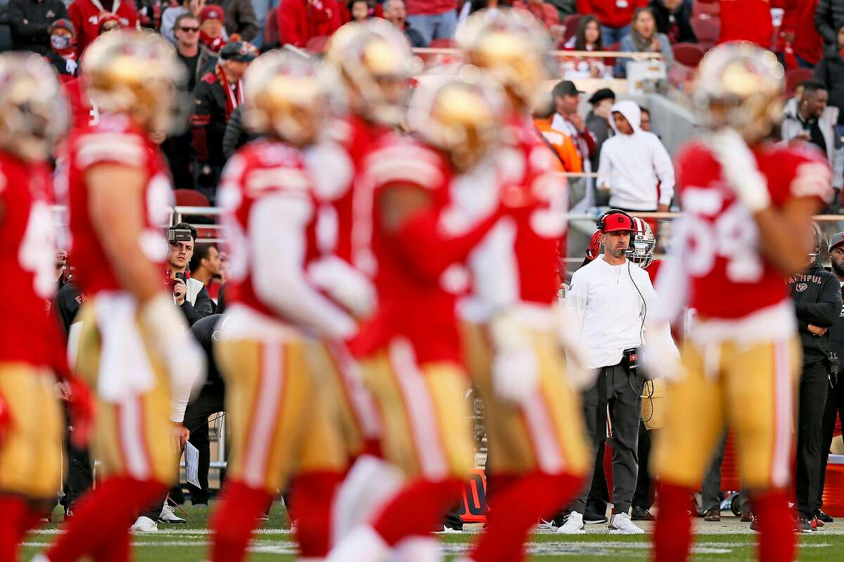 San Francisco 49ers head coach Kyle Shanahan is seen in the background as the 49ers huddle for a play call against the Minnesota Vikings in the first half of an NFC Divisional Round playoff game at Levi's Stadium on Saturday, Jan. 11, 2020, in Santa Clara, Calif.